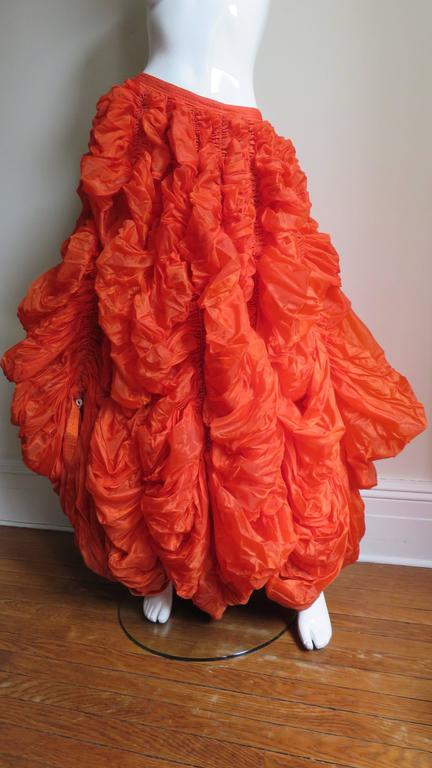 A rare item from Norma Kamali's noteworthy early OMO collection - a tangerine parachute skirt- one was exhibited at the MET in New York. Massive amounts of orange nylon with vertical lines of stitching containing white cord drawstrings around the