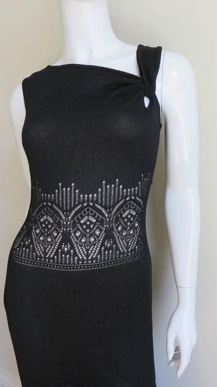 A great dress from John Galliano in a black with slight silver iridescence knit.  It has an asymmetric angled neckline and the midriff has cutouts in an abstract lace pattern around the circumference of the dress at the waist and hem.  Fitted