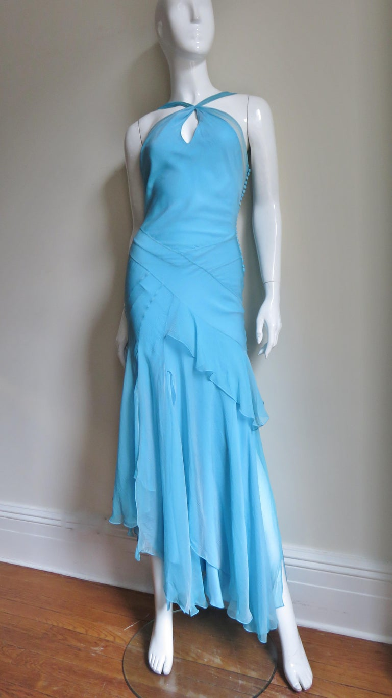 A gorgeous silk gown in the most stunning shade of blue.  A halter neckline with a tie at the neck, a sheer panel along the bodice sides and back and a keyhole front.  It has a multitude of seaming and angled panels at the waist and hips to enhance