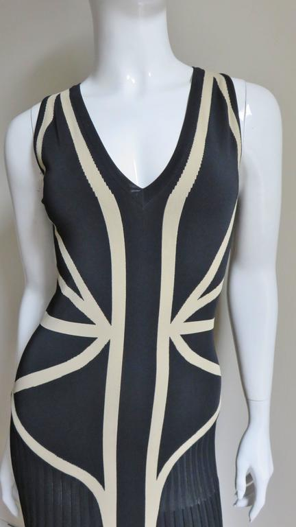 A very flattering dress from Alexander McQueen in back and beige stretch bandage fabric (think Herve Leger).  It is sleeveless with a deep V neck and fitted through to the thighs.  It is very flattering with the strategically placed lines of beige