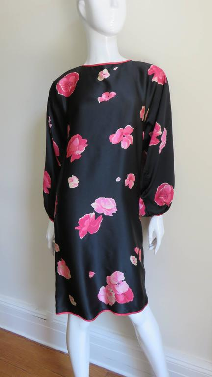 Simple dress from Geoffrey Beene in a black silk fabric with various flowers in pinks. The dress front is one piece of fabric and has a rounded neckline, dolman balloon sleeves with one button closure, keyhole back with tie at the neck and slightly