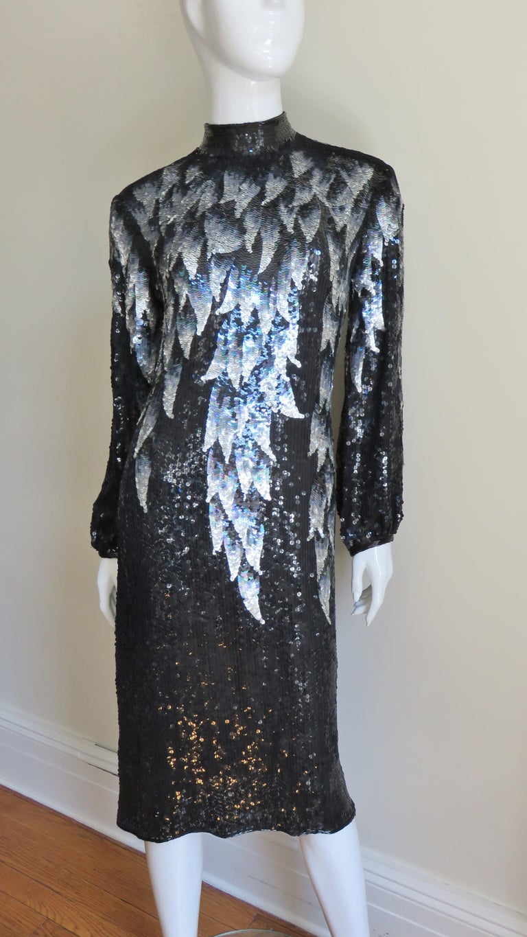 A fabulous sequin silk dress from Halston.  The background is comprised of black sequins throughout the dress with with an elaborate sequin pattern in shades of grey and silver raining down from the top of the dress front, back and sleeves.  The