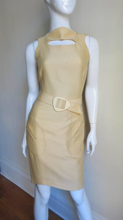 From Thierry Mugler in a soft butter yellow silk faille princess seamed fitted double yoke dress with a curved bateau neckline, a cutout at the upper chest and cut in shoulders.  It has a self belt with a matching yellow buckle, 2 welt patch pockets