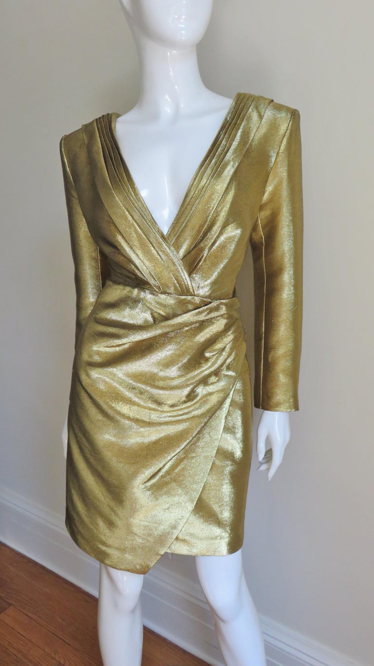 An incredible gold lame plunge front dress from Saint Laurent. It has a plunging front and back neckline framed in folds of the gold fabric crossing at the center front and back.  The skirt is softly draping and folds over one side at an angle.