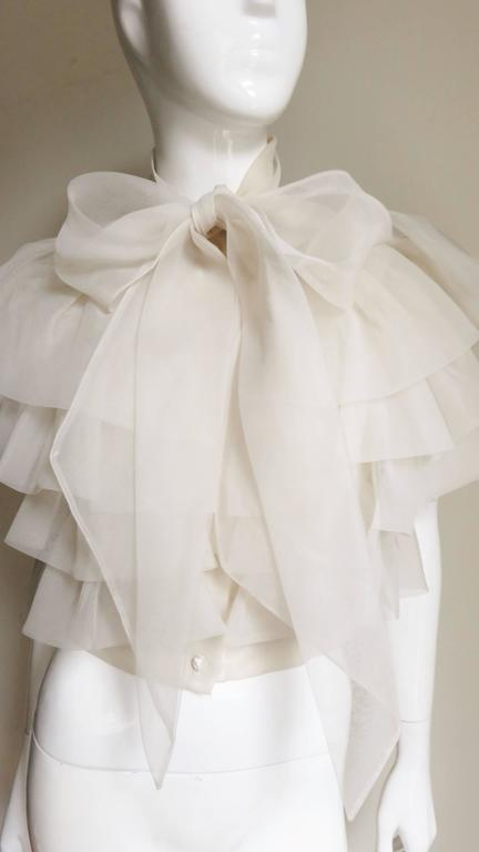 A very pretty ethereal ruffled blouse in off white silk. It has a tie at the neck then 4 cascading rows of ruffles beginning from the small yoke down to the waistband.  It has tiny off white rose buttons up the front.  Absolutely