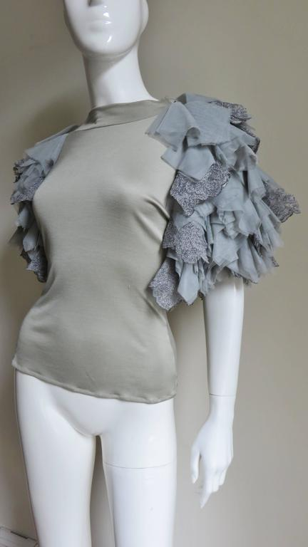 An incredible grey fine knit silk t-shirt from Alexander McQueen.  It has a crew neckline and the most elaborate grey net, tulle and lace appliqued layered sleeves.