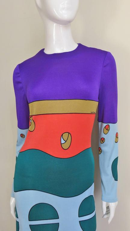 A full length long sleeved synthetic jersey dress by Louis Feraud with abstract shapes in greens, orange, blue, purple and black.  Long A line flattering dress skims the body flaring slightly at the hemline. Beautiful brightly color shapes
