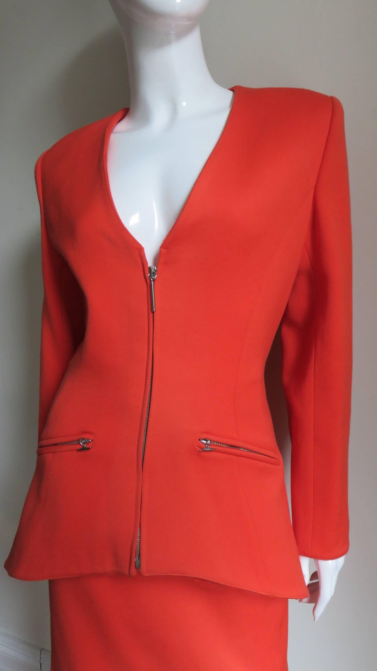 A gorgeous bright orange wool skirt suit by Claude Montana.  The V neck jacket has angled vertical seaming wrapping around the waist to the back creating a great fit.  It closes with a front silver metal zipper, has 3 silver metal rectangular