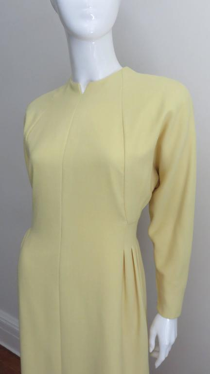 A pretty lemon chiffon colored light weight wool dress from Pauline Trigere.  It has a crew neck with a slit, light padding at the shoulders and dolman sleeves which close with hand attached zippers at the cuffs.  There is angled seaming on the