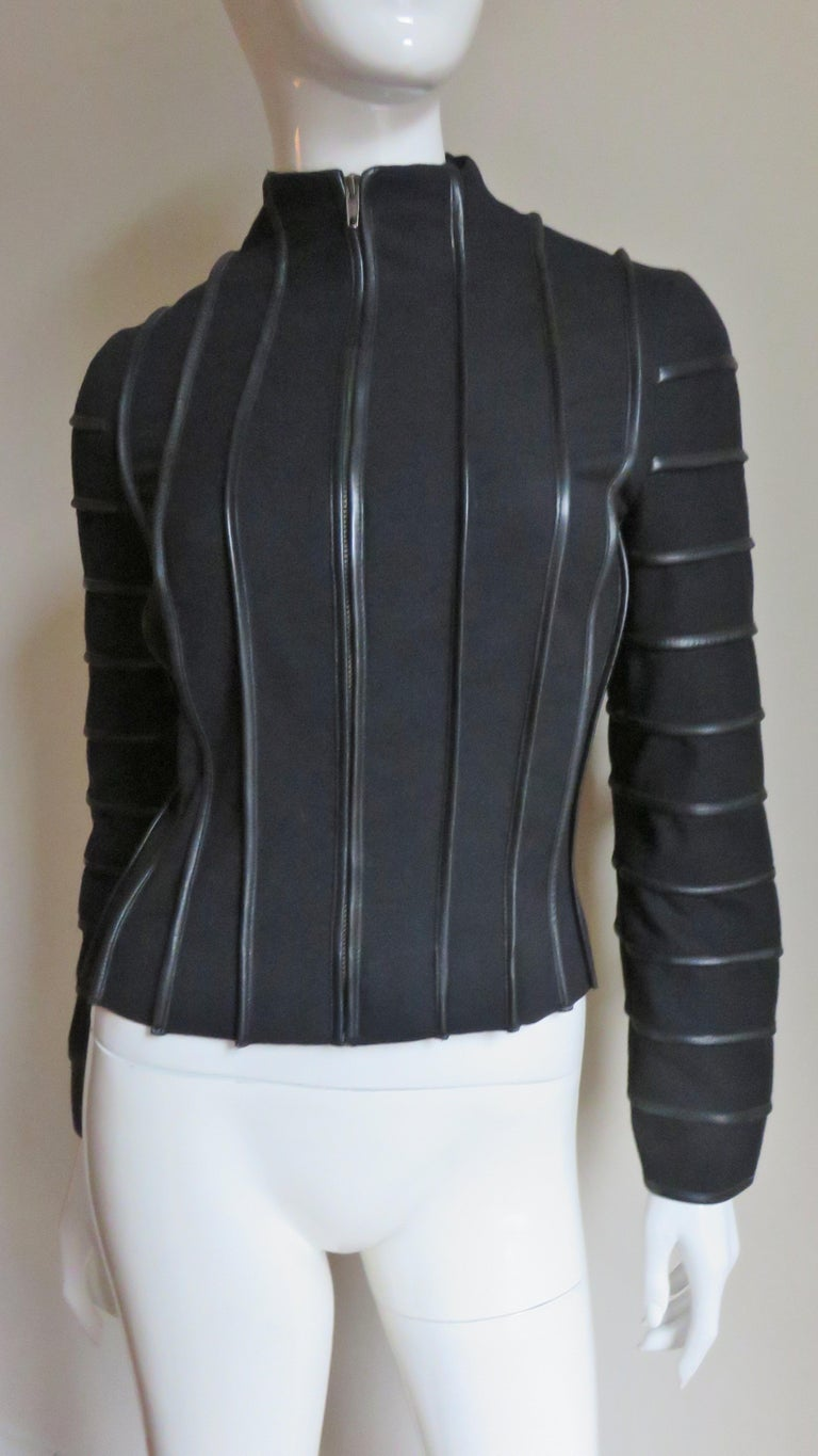 A great black wool jacket from Moschino.  It has a stand up collar and front zipper closing. The jacket is highlighted with vertical lines of black leather piping (horizontal on the sleeves) throughout contrasting nicely against the black wool.