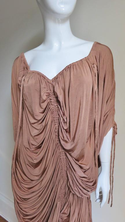 A soft warm tan silky rayon knit dress from Dolce & Gabbana. The dress has a V neckline front and back, adjustable length sleeves and an asymmetrical hemline. It is covered in gathers from drawstrings at the neck, sleeves, hem, shoulders and body