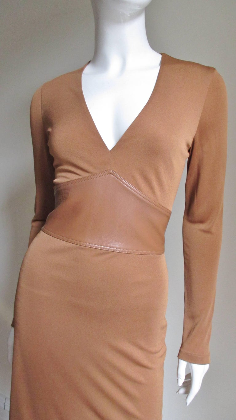 This is a stunning silk jersey dress from Gianni Versace Couture in a gorgeous caramel color.  It has a plunge neckline which meets an inverted V matching caramel leather inset waist in the front which is narrower in the back.  The skirt is