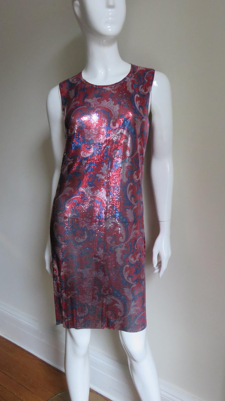 An incredible dress in red, blue and silver chain mail, metal mesh from the master known for his designs in metal wear,  Paco Rabanne.  It is a sleeveless shift with a rounded neckline and square cut armholes.  It is unlined and has 3 Rabanne