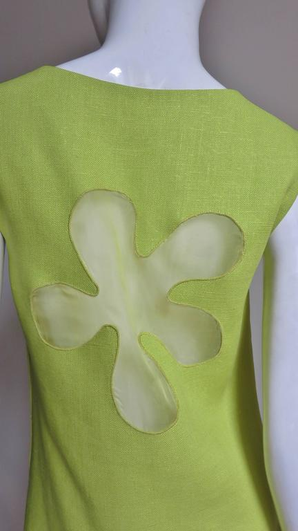 A mod 1960's dress in yellow/green linen by B. H. Wragge.  It is a simple sleeveless A line style with a fabulous cutout flower on the back covered in matching sheer silk.  The front has 2 bound pockets angled at hip level and it is lined in