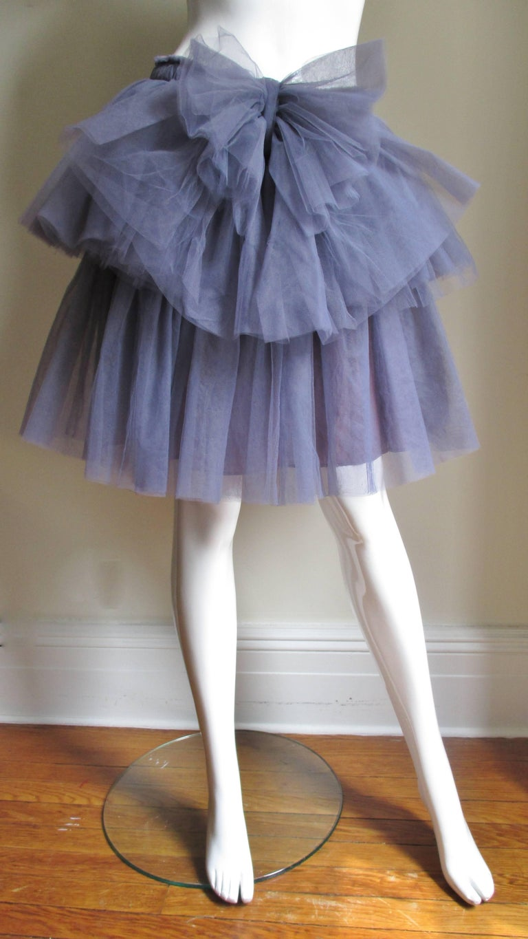A great purple tulle tutu sskirt from Valentino.  It has 2 full tiers of gathered tulle or netting with a net bow at the center front waist. It has a side zipper and purple lining.   New with tags unworn condition.  Fits size Small, Medium.  Waist