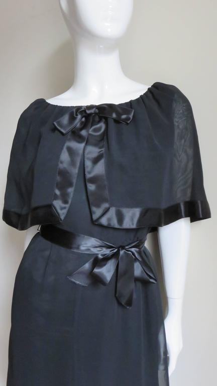A great black silk dress by William Travilla.  It has a rounded neckline with an attached gathered elbow length caplet edged in black silk satin.  It has a gathered  subtly A line skirt and has a matching black satin tie at the waist and neck. Fits