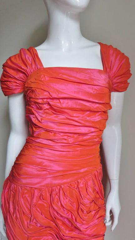 A gorgeous irredescent coral silk dress from vintage Louis Feraud.  In the light the silk changes in several shades of coral and rose coral.  The dress has gathered cap sleeves over the shoulders and ruching across the bodice from side to side.  The