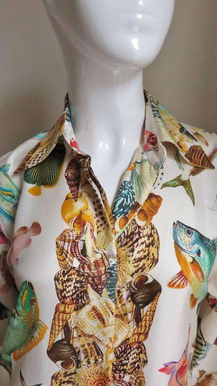 A beautiful silk shirt from Gucci.  The pattern is a beautiful conglomeration of different kinds and colors of fish with a mixed shells pattern along the center front, cuffs and hemline.  It has a shirt collar, button front and full sleeves with 1