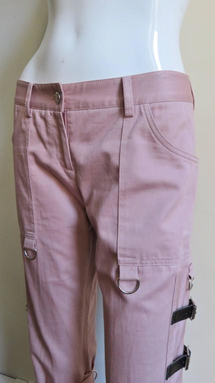 Beautiful pink cotton pants from Dolce & Gabbana.  They have a button waistband with loops, a zipper fly front and front patch pockets.  Below the pockets are side panels with functional adjustable leather straps and buckles, rings and a matching