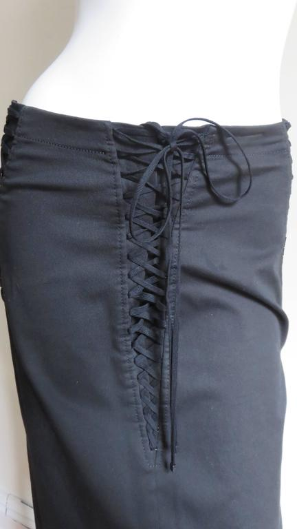 A great black cotton with slight stretch pencil skirt from Dolce and Gabbana.  It has lacing at both sides from waist to thigh and adjustable lacing in the center front. It is lined in black silk, has center back zipper and kick pleat.   Fits sizes