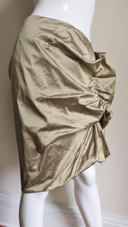 A fabulous gold silk skirt from Christian Lacroix.  It can be shaped in endless machinations by lengthening or shortening the drawstrings.  It is lined in the same fabric and has a side zipper.  Appears unworn condition.  Fits size Small,