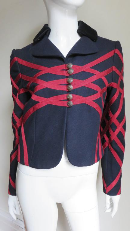 A great navy wool jacket from Moschino made with stunning red grosgrain ribbon appliqued in abstract geometric patterns front and back and along the sleeves.  It has a rounded lapel collar and center front hem plus heart and crown engraved brass