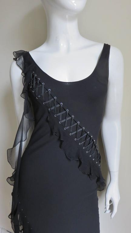 A fabulous black silk dress from Christian Dior. It has a scoop neck front and back with intricate lacing starting at each shoulder curving across the front/back around the hips to the hem. Additionally the lacing is highlighted with a small