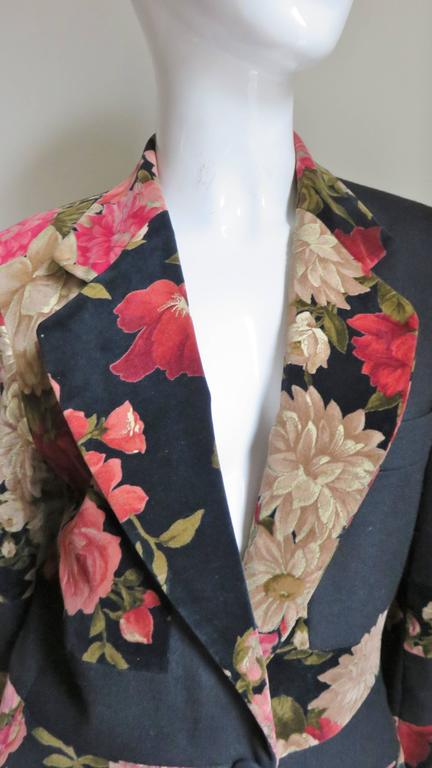 A great jacket from Moschino Couture.  It has an alternating pattern of red and gold flowers on velvet with solid black making it quite distinctive.  It is blazer style jacket with 2 front flap pockets, a breast pocket, lapels and slight shoulder