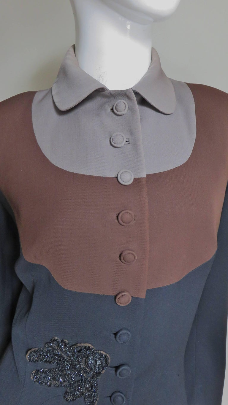A great jacket from Eisenberg Originals in taupe, brown and black wool.  The colors are placed in curved horizontal panels on the front and back- a small taupe, then a larger brown and the rest of the jacket is black.  It has self covered buttons