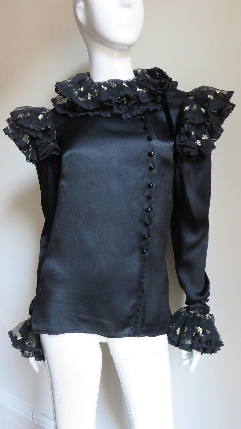A gorgeous black silk charmeuse blouse shirt blouse by Valentino.  It buttons asymmetrically off center front with delicate faceted black glass buttons and is adorned with varying layers of beautiful gold flower dotted black lace at the neck,