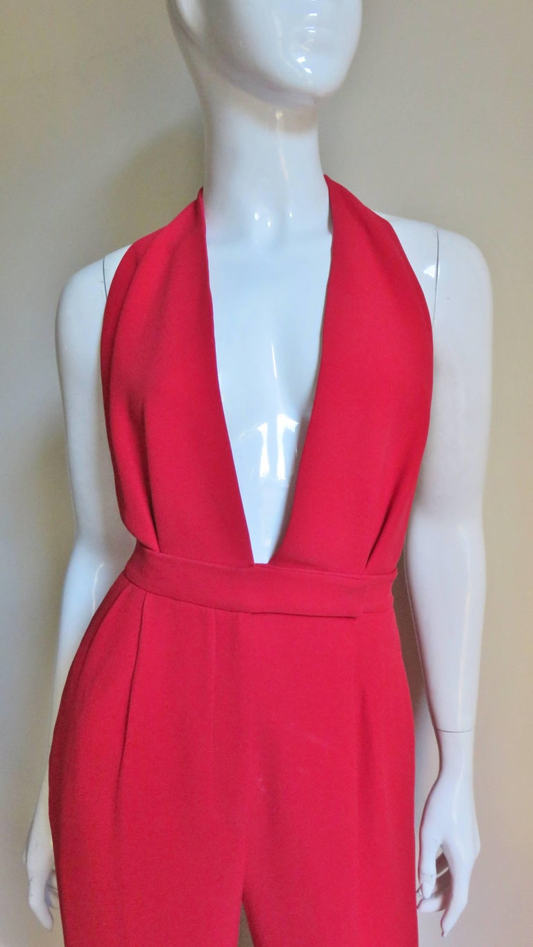 An incredible red silk jumpsuit from Valentino.  It is halter style with a plunging neckline to the waist.  The bodice has 2 front tucks as do the pants at the waistband that joins them.  The legs are full.  The jumpsuit has side seam hip and back