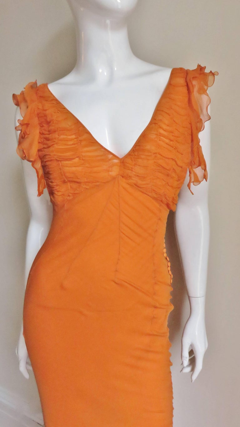 An absolutely stunning orange silk gown by John Galliano for Christian Dior.  It has a plunging neckline front and back plus deep armholes with ruffle edges.   The bust portion of the dress has horizontal ruching. The body of the dress is fitted