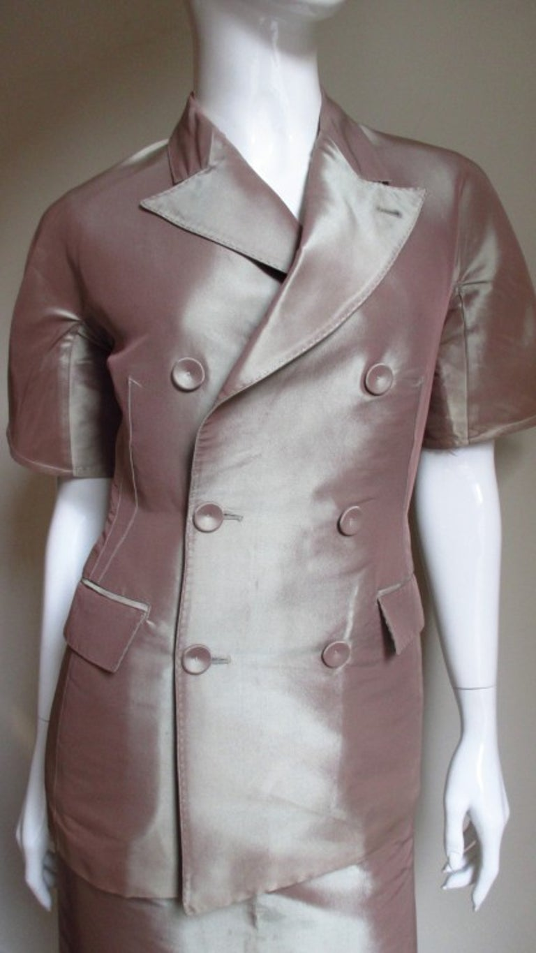 A skirt and jacket suit in iridescent blush silk twill from Jean Paul Gaultier. The double breasted peak lapel jacket is short sleeved with 2 welt flap pockets, 6 self covered buttons and hand stitched detail on the lapels and pocket flaps.  There