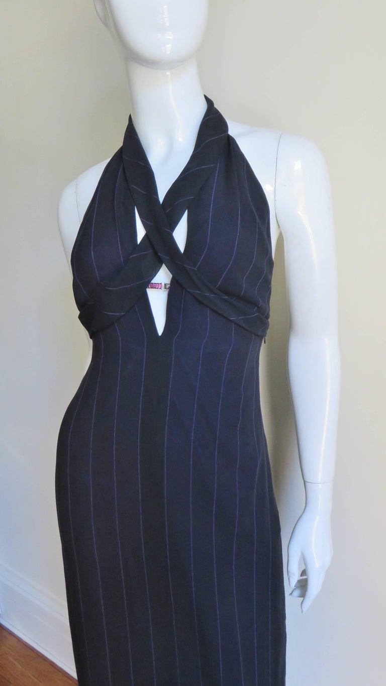 A fabulous black with fine violet stripes silk dress from Gianni Versace.  It has a plunging halter neckline with 2 bands of fabric crossing the chest, wrapping under the bust.   A fine silver metal purple glass stone bar is located mid cleavage