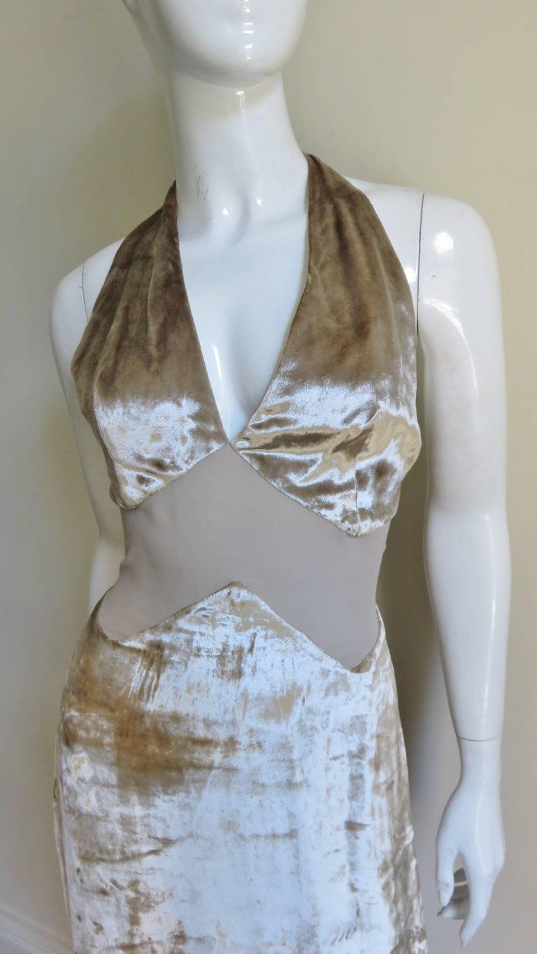A fabulous beige silk vekvet halter dress from Gianni Versace. It has a matching semi sheer silk inverted V cutout midriff.  The neckline plunges into a low V in the front and to the waist in the back. It is lined in matching silk lining and there