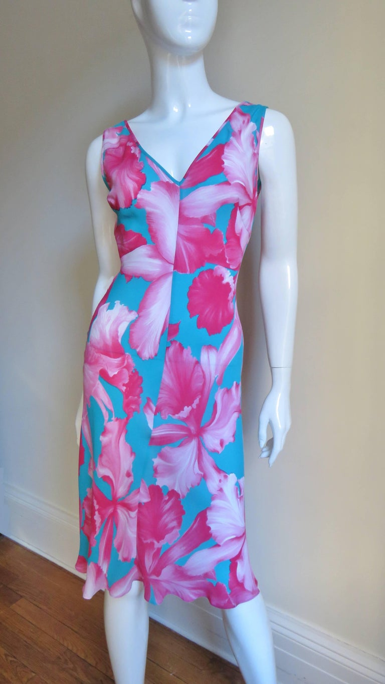 A gorgeous silk pink and turquoise tropical flower print dress with a matching silk fringe wrap/tie belt from Celine.  It is sleeveless with a plunging V front and deeper V in the back. It is semi fitted through the waist then flares to the hem and