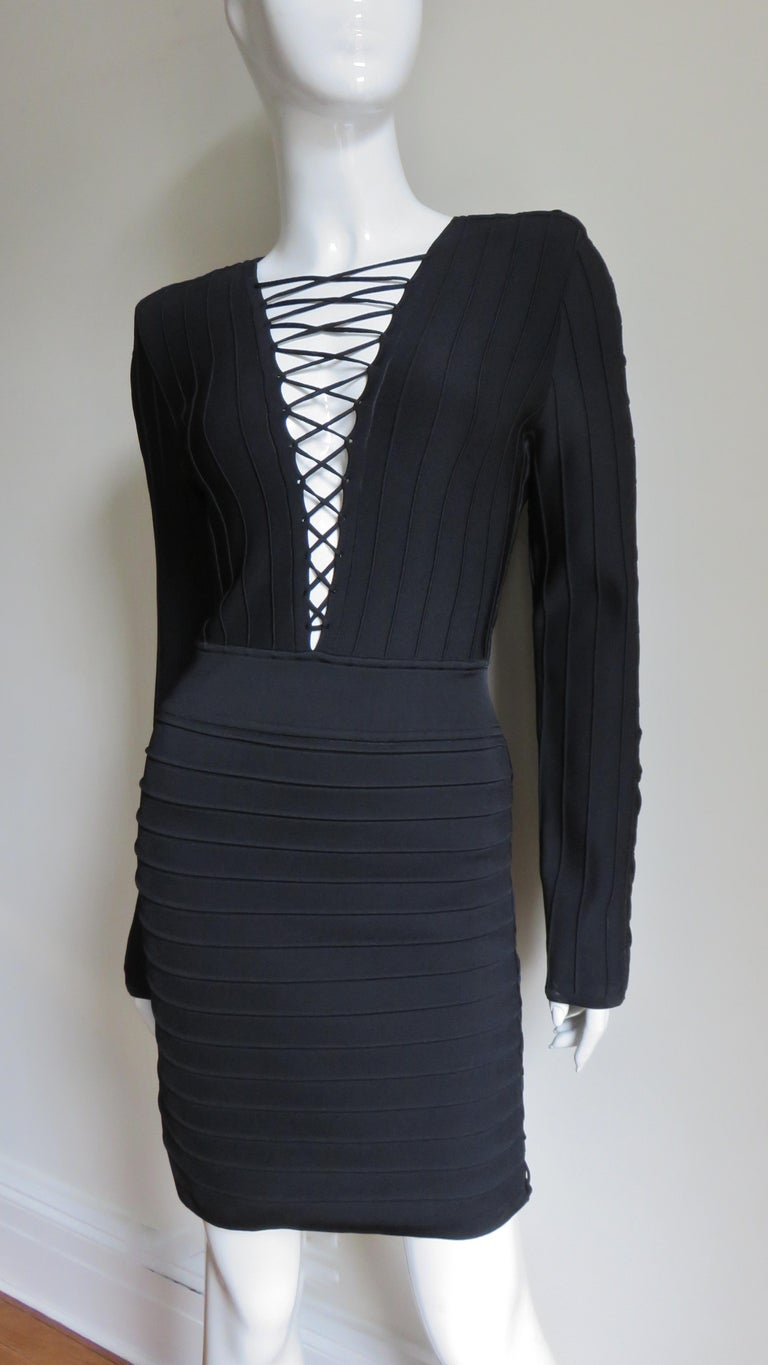 A fabulous black bandage dress from Pierre Balmain.  It is a fitted dress with front lacing through to the waist.  There is decorative lacing along the tops of the shoulders through the sleeves to the wrists and from underarm to hem.  Gorgeous!  It