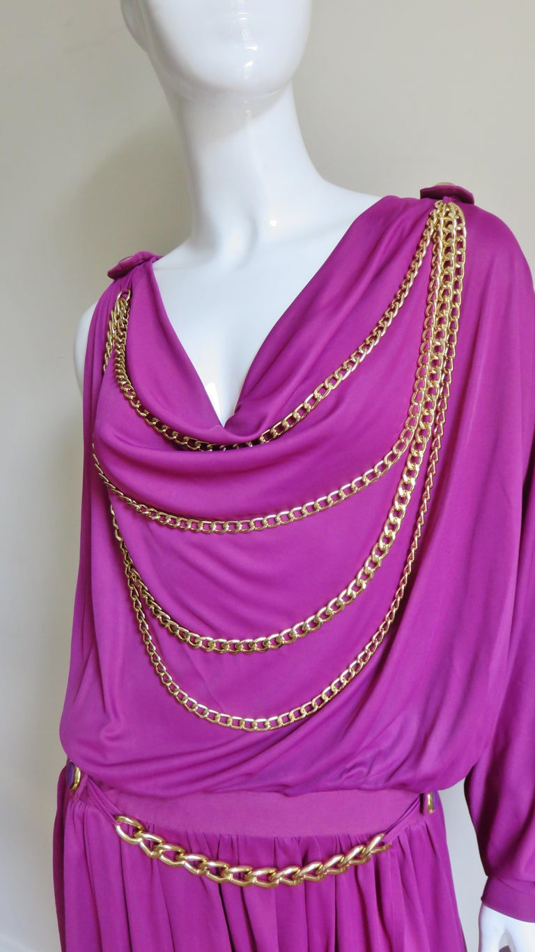 A fabulous pink purple jersey dress from Dolce & Gabbana D & G line.  It has a drape neckline front and back adorned with rows of draping gold chains with an additional one crossing the upper back and front waist. The dress has a drop waist, one