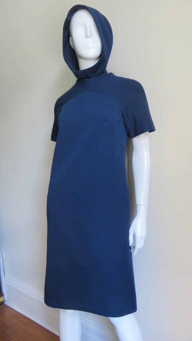 A blue wool jersey dress from Pauline Trigere with a matching hood.  The dress has a simple crew neckline, short sleeves, an inverted V seam at the upper chest and back and a back zipper.  The matching hood slips on zipping closed up the center