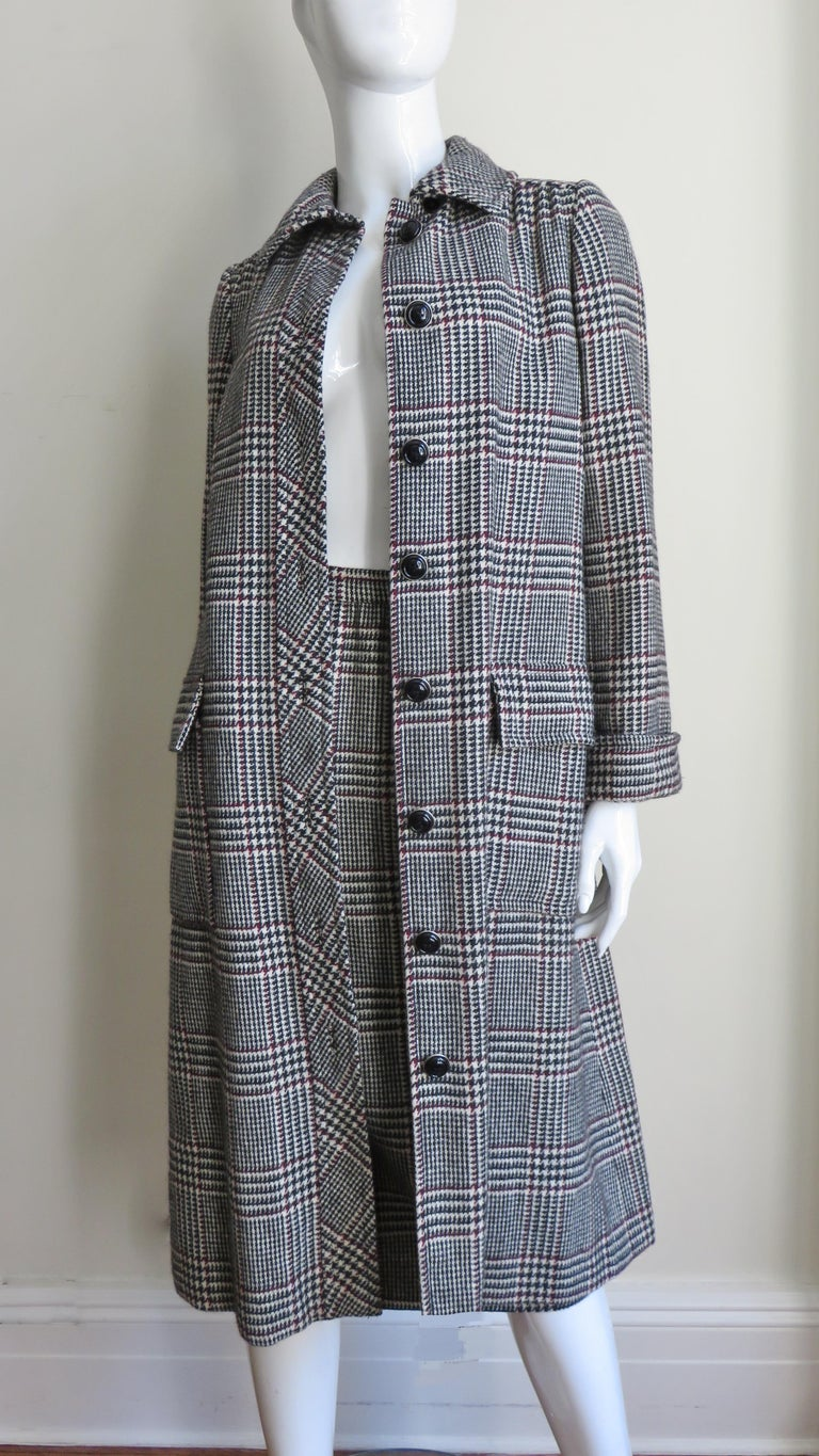 A fabulous coat and skirt set from Adele Simpson in off white, burgundy and black plaid wool.   The coat has 2 front flap patch pockets, a small collar, fold back cuffs with 2 buttons, a back yoke and a matching tie belt.  It close up the front with