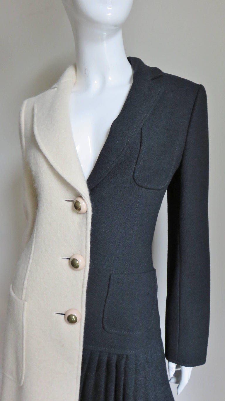 This is a fabulous half black, half off white wool coat from Moschino.  It has a lapel collar and hip patch pockets, the black side also has a breast pocket.  The off white side has a slight A line and the black has a pleated panel from hip to hem.