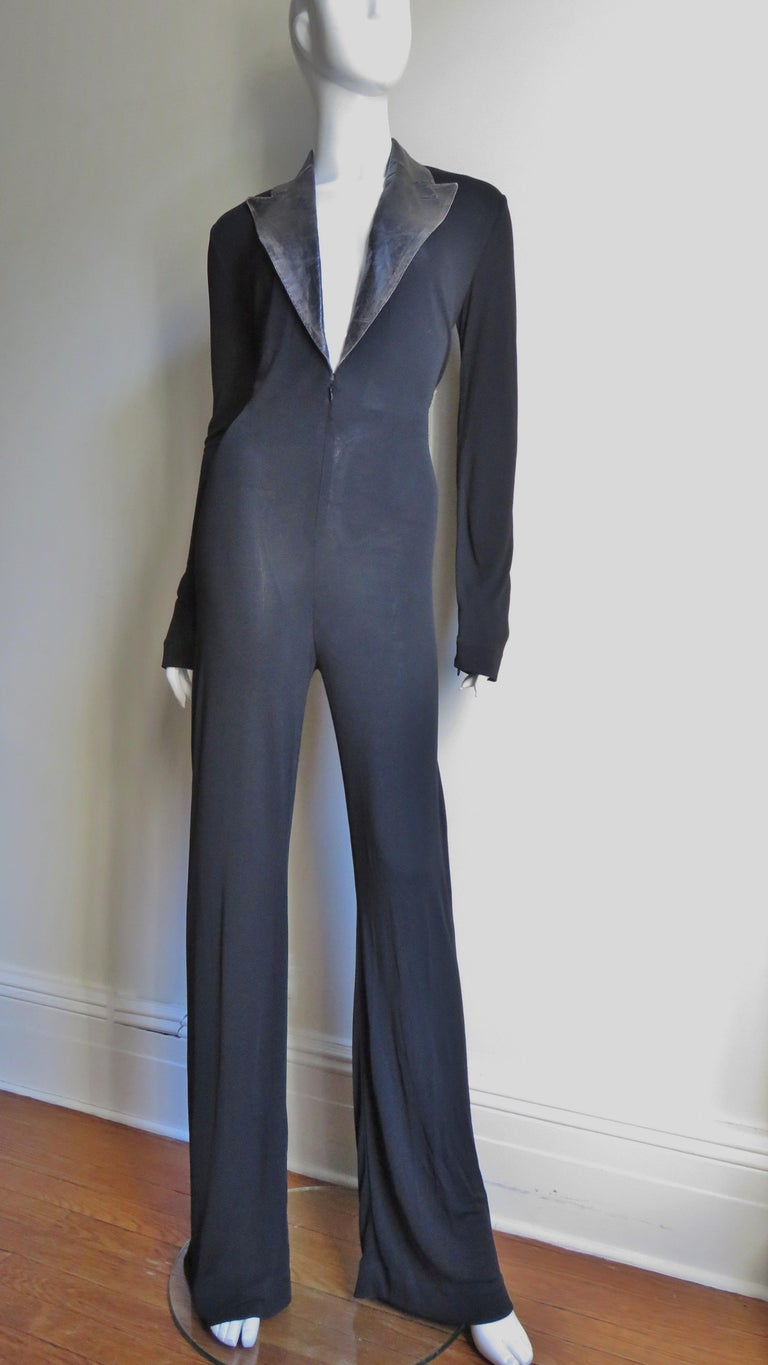 A fabulous black jersey jumpsuit from Jean Paul Gaultier.  It has a plunging neckline with a leather peak lapel collar.   The jumpsuit skims the body with long sleeves and full legs.  There is an inner belt securing the front in place, a zipper