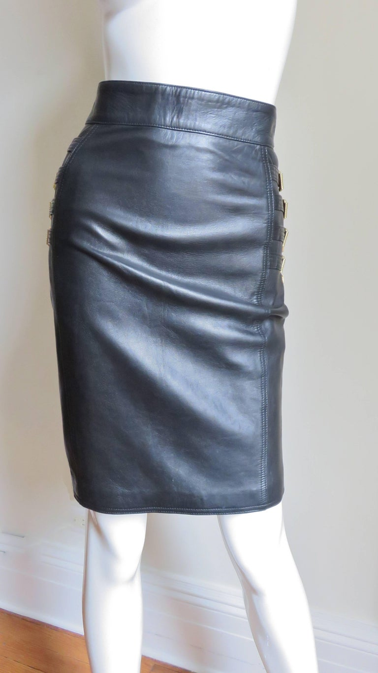A soft, supple, black leather skirt from Gianni Versace's 1994 collection.  Each side of the hips is adorned with 4 intricately detailed multi top stitched functional, adjustable straps with gold metal buckles, tips and loops (each has one gold and