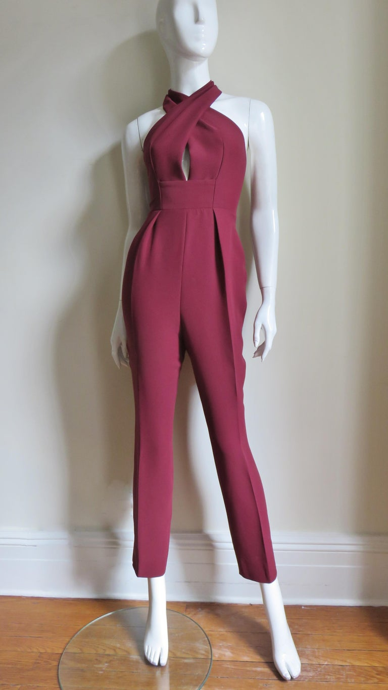 A fabulous burgundy silk jumpsuit from Gucci.  It is halter style crossing at the front then wrapping around the neck leaving a hole at the center front cleavage.  There is a band at the waist then fitted crop pants with a tuck on either side of the