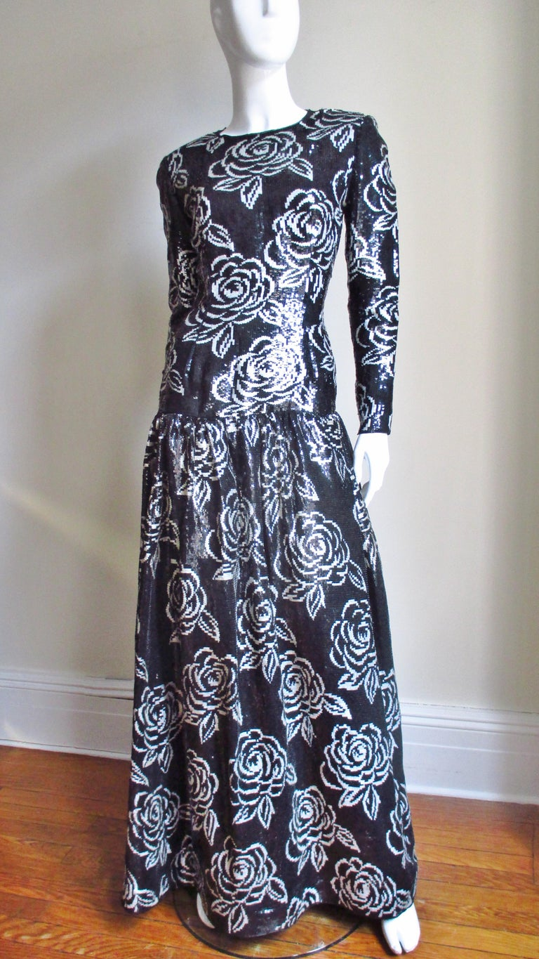 A black and white sequin gown by Oscar de la Renta.  It has long sleeves with zippers at the wrists, a flattering fitted drop waist bodice and a gathered skirt all completely covered in black and white sequins on silk in a beautiful flower pattern.