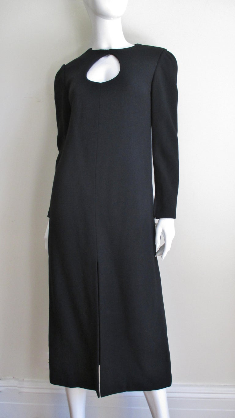 An early 1970s midi length black wool dress from Pierre Cardin.  It has long sleeves with a tear drop shape cutout at the chest then flaring gently to the mid calf.  It has a center front slit, is fully lined in black and has back zipper. Appears