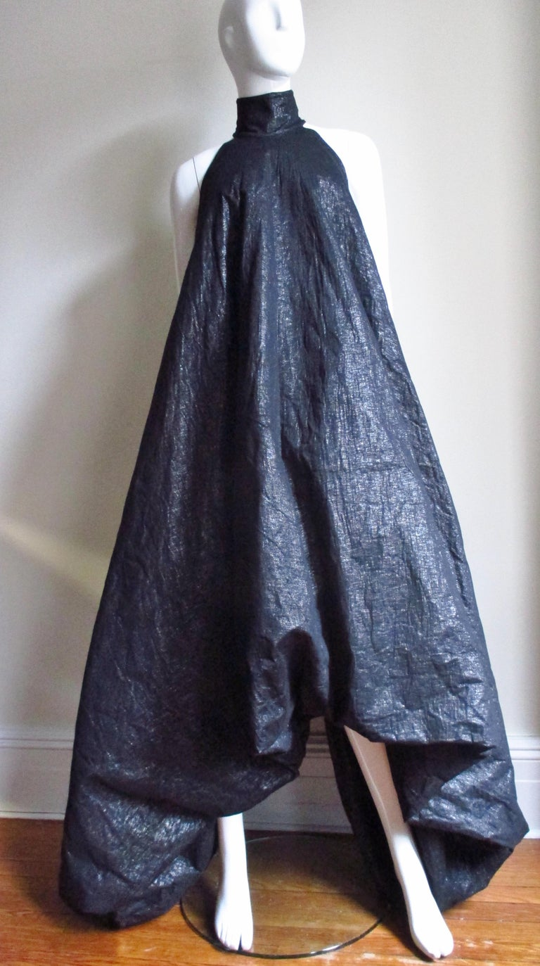An incredible dress from designer Gareth Pugh. It is made of black coated cotton/silk blend with a subtle silver shine.  The silhouette is dramatic- narrow at the stand up collar with cut in shoulders then becoming wider towards the hemline which is