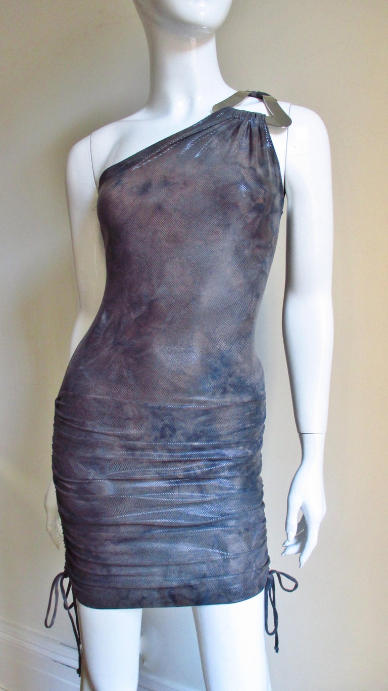 A muted shades of grey fine jersey dress from Gianni Versace Couture with a large silver metal triangle at the shoulder holding the front and back straps.  It is bare on the other shoulder, fitted through to the hips where it has side drawstrings to