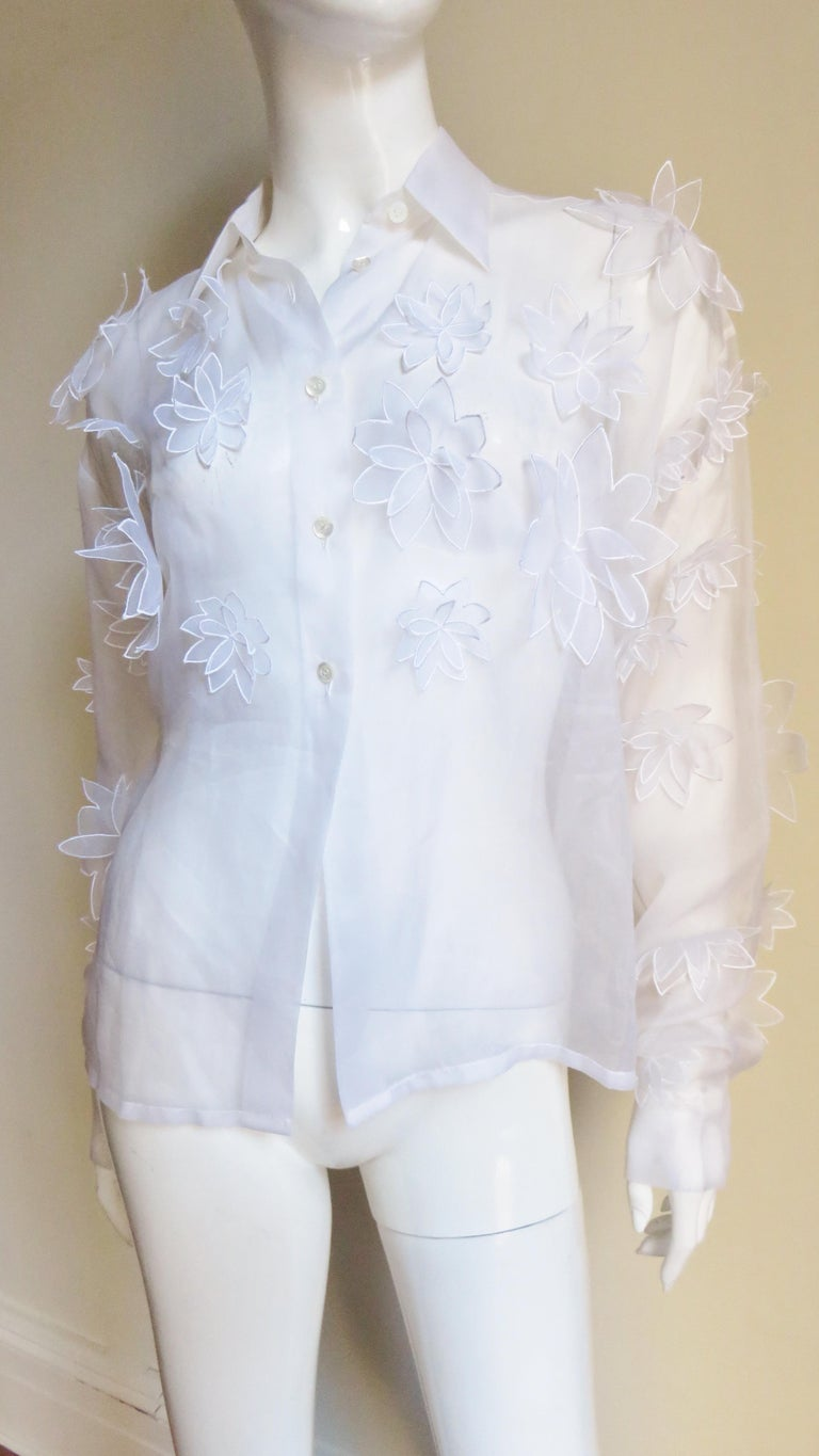 A stunning white semi sheer silk shirt, blouse from Dolce & Gabbana.  It has a shirt collar and long sleeves with button cuffs.  The sleeves, upper front and back are covered in intricate layered flowers of the same fabric in varying sizes.  The