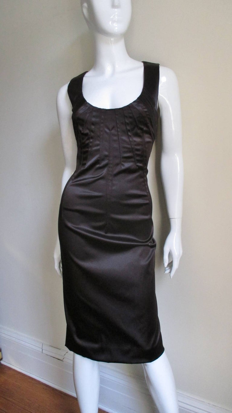 A Dolce & Gabbana silk fitted dress in a rich dark brown with elaborate top stitched darting detail fanning out from the scoop neckline front and back.  It has a center back zipper and leopard silk lining.  Fits size Small, Medium.  Bust  34